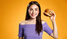 Takeaway Food Delivery Concept. Happy Girl Holding Hamburger And Smiling. Hungry Young Woman Eating Cheeseburger From Favorite Restaurant. Female Student Grab Lunch Tasty Burger, Orange Background
