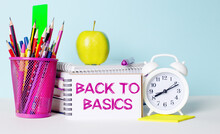 On A Light Table There Are Books, Stationery, A White Alarm Clock, An Apple. Next To It Is A Notebook With The Text BACK TO BASICS. Educational Concept.