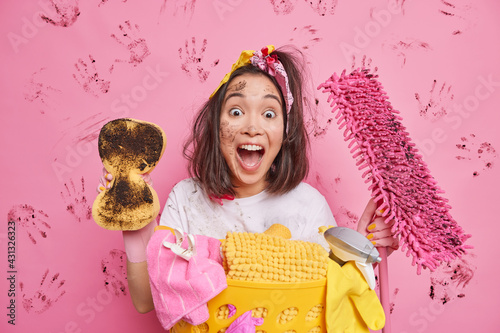 Fotografia Emotional cheerful housewife exclaims loudly rubs dust in room holds dirty sponge and mop does laundry tidies up house poses against pink background