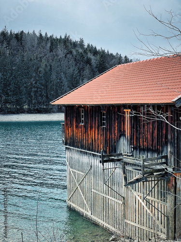 Canvas wooden boathouse in water with trees in the background