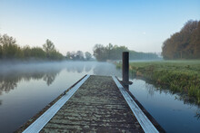 Horizontal View On A Pier In Small River Linge During Blue Hour In Spring, With Trees On The Horizon And A Meadow. Morning Haze And Reflections On The Water. Betuwe In Netherlands With Copy Space.