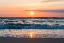 Orange Sunset At The Beach With Sand And Waves In The Forground And Reflection In The Shallow Water