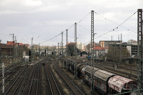 Fototapeta train railroad tracks with parking wagons and electric power lines, symbol for urban vibes and industry obraz na płótnie