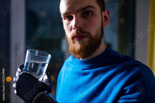 Canvas young man with modern biotechnology hand in apartment holding water glass