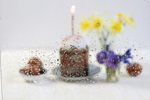 View Through Glass With Water Drops On Easter Cake, Burning Candle, Eggs, Yellow And Blue Flower Bouquets In Vases On White Background