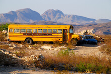 Typical Old Yellow School Bus Parked In The Desert Next To A Junk Car
