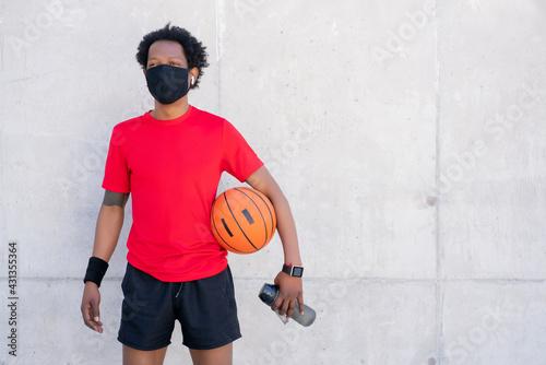 Naklejka premium Afro athletic man holding basketball ball.