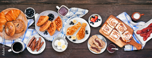Fathers Day brunch table scene. Top view on a dark wood banner background. Tie pancakes, mustache toast and an assortment of dad themed food.