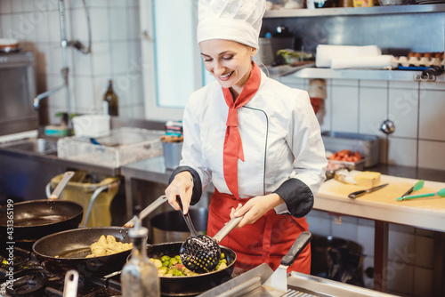 Woman chef with pans and pots preparing food in the restaurant kitchen