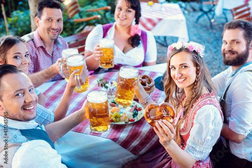 Billede på lærred Group of people in proper Tracht drinking in Bavarian beer garden