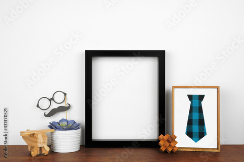 Mock up black frame with rustic Fathers Day theme decor. Wood shelf against a white wall. Copy space.