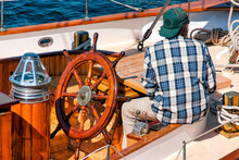 Man In Plaid Shirt And Hat Sitting Back To At The Wooden Helm Of Sailboat