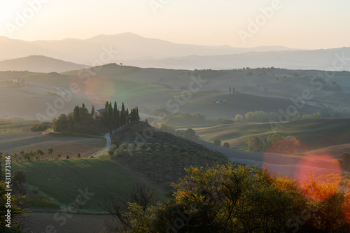 Fototapeta premium A stunning landscape view on an autumn morning of the hills of Tuscany with ploughed and green grass covered with beautiful undulating fields. The sunlight covering the meadows and fields makes