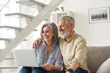 Happy Older Mid Age Family Couple Using Laptop Sit On Couch. Smiling Senior Adult Mature Man And Woman Looking At Computer Doing Ecommerce Online Shopping, Watching Tv, Having Virtual Chat At Home.