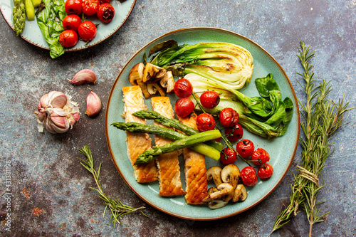 Fotografering grilled salmon with vegetables, tomatoes, asparagus on a turquoise plate, dark b