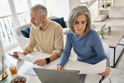 Serious mature senior old couple reading documents bills paying bank loan online together using laptop and phone, calculating pension taxes, planning family retirement money finances working at home.