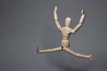Horizontal Conceptual Photography Of A Single Wooden Mannequin Man While Happy Jumping Against Gray Background