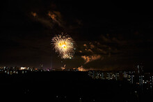 Yellow Firework And Smoke Over Apartment Houses And Forest With Other Fireworks In The Background