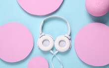 White Stereo Headphones On A Blue Background With Pink Circles. Minimalistic Modern Music Layout