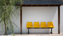 Four Yellow Seat On Metal Stand Under Wooden Roof With White Wall And Tree On Tile Floor. Place For Relax In The Park