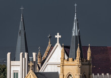 Two Spires With Crosses And Crucifixs On Ornate Church Roof With Turrets Bathed In Sunlight Deep Grey Stormy Smokey Sky
