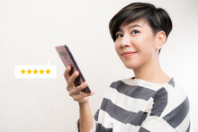 Customer Experience Ratings Concept. An Asian Woman Using A Smartphone To Submit Stars Feedback, And Review To Products Or Services She Quite Satisfied. Marketing Business Important Tools. Surveys.