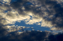 White Clouds And Light Ray Behind Cloud With Blue Sky