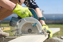 Carpenter Working With A Circular Saw Outside In Sunny Day. Worker Sawing Wood Board With Electric Circular Saw. Close-up