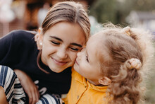 Photo Of Two Little Sisters 3 And 11 Years Old Embracing With A Smile For A Photo