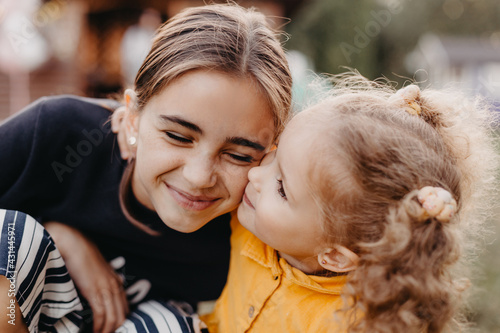 Fotografie, Tablou photo of two little sisters 3 and 11 years old embracing with a smile for a phot
