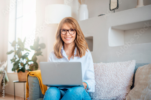 Fototapeta Happy middle aged woman using her laptop while sitting on the sofa at home obraz
