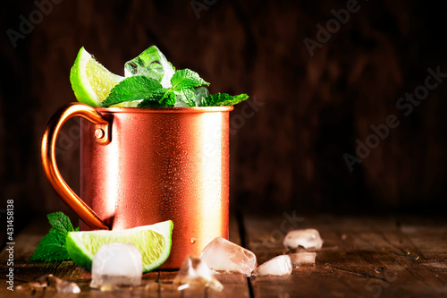 Moscow mule or mint julep alcoholic cocktail in copper mug with lime, ginger beer, vodka and mint. Wooden table, copper bar tools - fototapety na wymiar