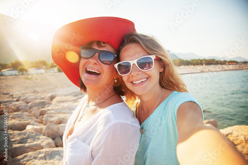 Fototapeta Happy people, Mother And Adult Daughter Making Selfe On The Beach Traveling Together obraz