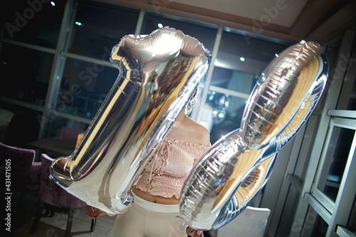 Fotografie, Obraz Debutante holding number 18 silver balloons posing indoors