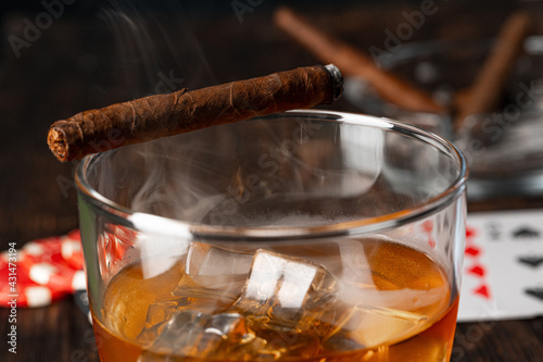 Obraz Cuban cigar, whiskey glass and chips on table - fototapety do salonu