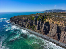 A Stunning Aerial Shot Of The Coastline With Vast Blue And Green Ocean Water, Lush Green Hillsides With Homes And Waves Crashing Into The Beach At Baby Beach In Dana Point California