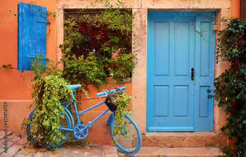 Fototapeta Rovinj, Istria, Croatia. Old blue bicycle at street near door of entrance in house among green bushes and flowerpots with flowers. Picturesque cosy lane. Window shutters on windows. obraz