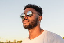 Face Portrait Of A Handsome Black And Young American Man Wearing Sunglasses And Smiling During Sunset At The Beach