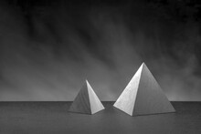 Two Wooden Pyramids As  Geometric Objects On Gray Background With Fog. Bw Photo. Studio Shot