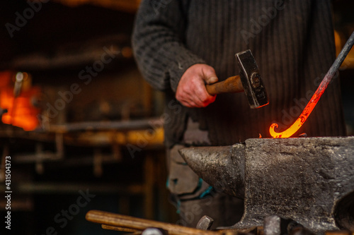 Fotografia The blacksmith twists the spiral with a sledgehammer, placing a red-hot iron blank on the anvil