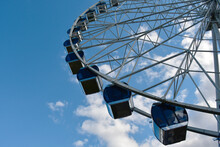 Part Of The Ferris Wheel With Closed Booths Against A Background Of Blue Sky And Clouds
