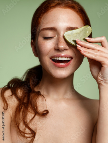 Obraz Vertical shot redhead beauty girl with glowing skin, holding natural jade gua sha scraper, smiling, tcm chinese traditional medicine on facial skin, self massage relieve muscle tension - fototapety do salonu