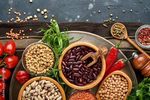 Legumes, lentils, chickpea, beans assortment, tasty appetizing ingredients spices grocery for cooking healthy kitchen on black table Fototapet