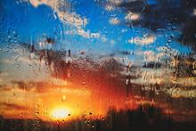 Bright Summer Sunset Behind Dripping Glass After Rain.