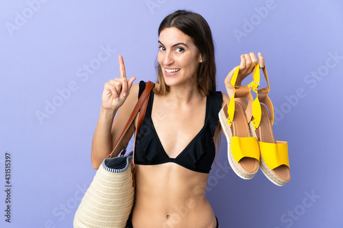 Young caucasian woman with a beach bag holding a sandals isolated on purple background pointing up a great idea