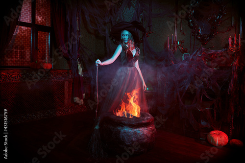 Foto witch conjures over cauldron