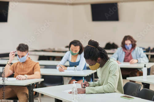 Fototapeta Side view portrait of young African-American man wearing mask while taking test or exam in school with diverse group of people, copy space obraz
