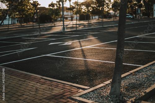 Fotografering Aparcamiento de coches vacío al atardecer frente a gran edificio