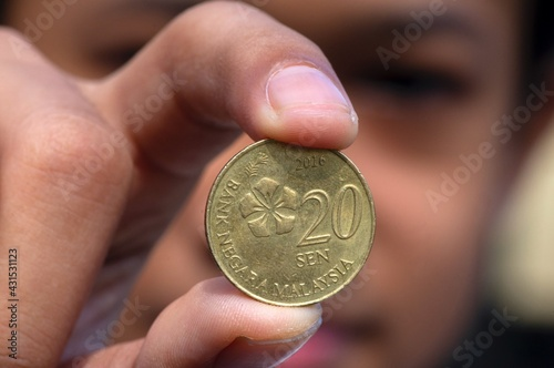 Fototapeta Asian child hand holding a 20 sen Ringgit Malaysia coin, selected focus and blurred background obraz