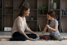 Little Teen Girl Child And Young Caucasian Mother Or Nanny Sit On Floor At Home Play On Weekend Together. Happy Mom And Small Teenage Daughter Have Fun Engaged In Funny Game Activity In Living Room.